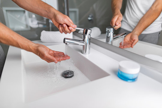 Hot water running from bathroom sink faucet man checking pressure and temperature washing hands in modern home lifestyle.
