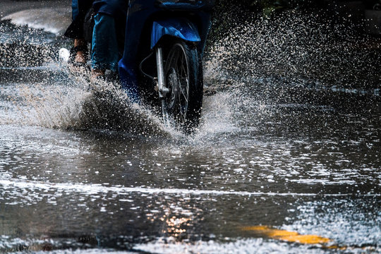 motion motorcycle  rain big dirty puddle of water spray from the wheels