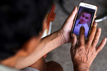 Hoang Van Lanh, father of Hoang Van Tiep who is one of the suspected victims of the 39 people found dead in a refrigerated truck in Britain shows his pictures on a mobile phone at his house