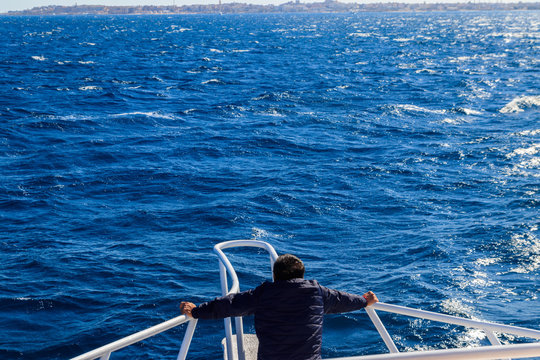 Man standing on the white bow of yacht and looking on sea or ocean. Luxury vacation concept. Back view