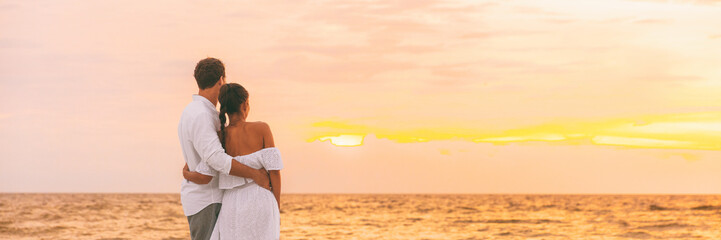 Honeymoon couple walking on romantic evening watching sunset banner panorama background. Beach wedding woman wearing white dress and elegant man lovers relaxing on Caribbean vacation travel panoramic.