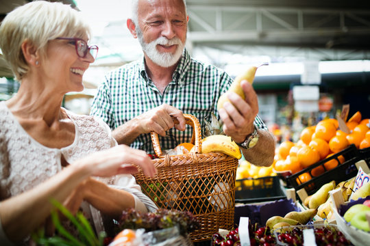 Only the best fruits and vegetables. Beautiful mature couple buying fresh food on market