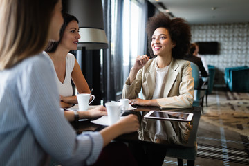 Successful attractive women friends chatting in cafe during coffee break