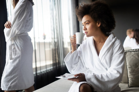 Woman relaxing and drinking tea in robes during wellness