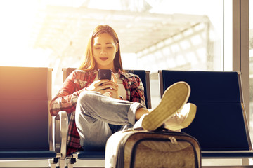 Air travel concept with young casual girl sitting with hand luggage suitcase. Airport asian woman on smart phone at gate waiting in terminal.