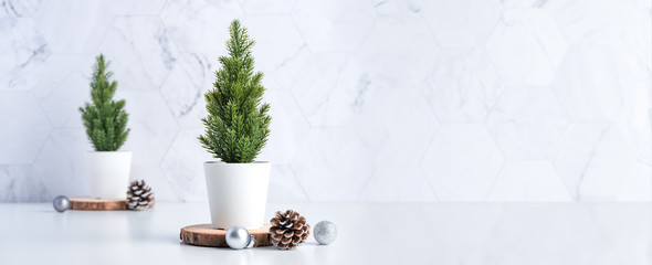 christmas tree with pine cone,decor xmas ball on wood log at white table and marble tile wall...