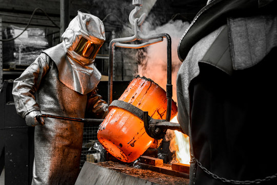In a foundry workshop. A worker protected by a safety suit pours the molten metal into a mold