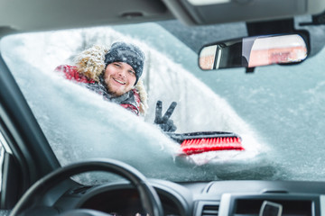 cleaning car after snow storm smiling man with brush