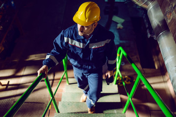 Full length of caucasian worker dressed in blue work suit and with protective helmet on head climbing up the stairs. Energy plant interior.