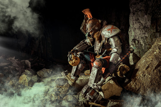 Powerful knight in the armor with the hammer is sitting on the stone. Dungeon on the background.
