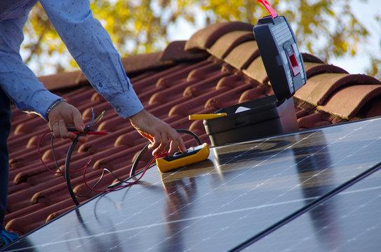 Technician installs solar panels on the roof