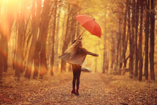 young woman dancing in an autumn park with an umbrella, spinning and holding an umbrella, autumn walk in a yellow October park