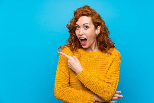 Redhead woman with yellow sweater surprised and pointing side