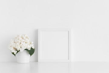 White square frame mockup with a hortensia in a pot on a white table.