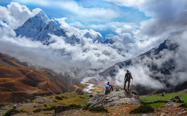 Fototapeta Active hikers hiking, enjoying the view, looking at Himalaya mountains landscape.Tracking to Everest base camp valley with Ama Dablam view. Travel sport lifestyle concept obraz