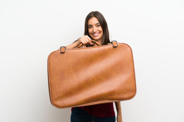 Young woman over isolated white background holding a vintage briefcase