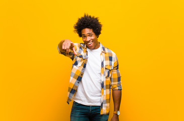 young black man pointing at camera with a satisfied, confident, friendly smile, choosing you against orange wall Wall mural