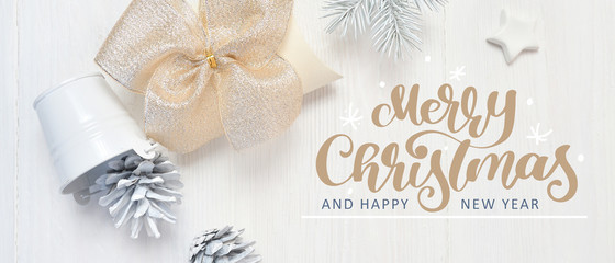 Mockup Christmas white tree, beige bow and cones with calligraphy text Merry Christmas. Flat lay on...
