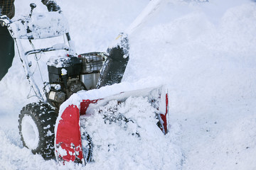 A man removing or cleaning snow from street with snowblower detail.