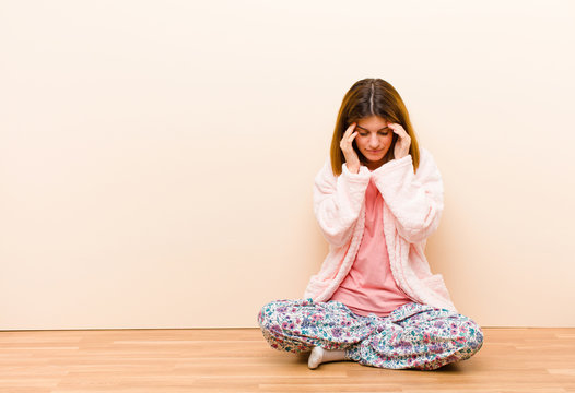 young woman wearing pajamas sitting at home looking stressed and frustrated, working under pressure with a headache and troubled with problems