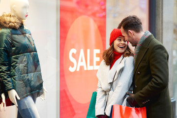 Happy couple during the window shopping in wintertime