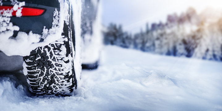 Winter tire panorama detail in snowy mauntains. Car tires in snow with sun lights in background.