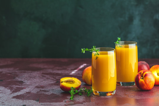 Glass of fresh healthy peach smoothie or juice on dark concrete surface table