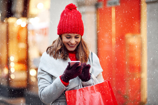 Beautiful woman using mobile phone during shopping in wintertime