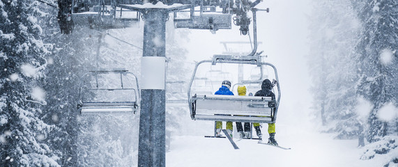 Papiers peints Glisse hiver Three skiers on ski lift in heavy snowing storm. Beautiful vacation in winter mountains.