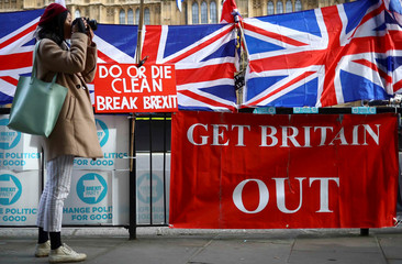 A woman takes pictures next to pro-Brexit placards outside the Houses of Parliament in London