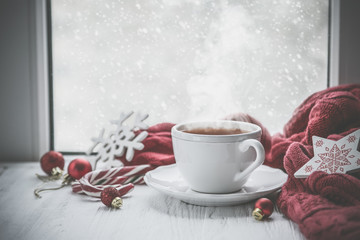 Foto op Plexiglas Thee Winter cozy hot chocolate in front of window, snow, sweater. Lazy weekend, love, comfort