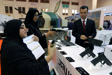 Bahraini women check Jordanian made pistols at Jordanian Military stand at the Bahrain International Defense Exhibition and Conference in Manama