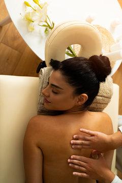 Vertical shot pretty dark hair woman on massage , top view