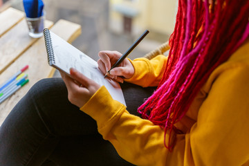 Unrecognizable person, girl artist, illustrator draws in notebook, makes sketch. Close-up of woman with long pink dreadlocks in informal setting, in casual comfortable clothes sitting in cafe