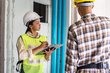 Team of Inspector holding clipboard opening paper and checking building for renovation, engineer surveyor looking in construction site. Home inspection consultancy concept