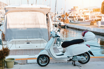 Scooter A white retro scooter stands on a pier