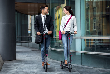 Two smiling business people driving electric scooter in front of modern business building going on...
