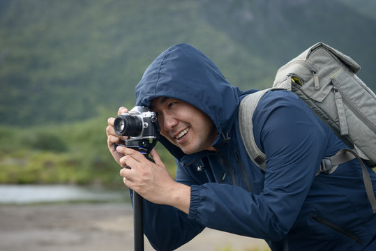 Asian photographer taking photo with tripod in winter season, lifetyle concept.