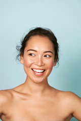 Beauty face. Smiling asian woman with perfect skin portrait. Beautiful happy girl model with healthy glowing facial skin and natural makeup and white smile on blue background at studio