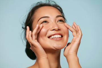 Skin care. Woman with beauty face touching healthy facial skin portrait. Beautiful smiling asian girl model with natural makeup touching glowing hydrated skin on blue background closeup Fotoväggar