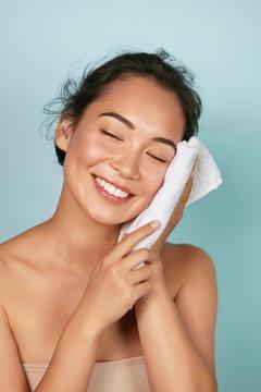Washing face. Closeup of woman cleaning skin with towel portrait. Beautiful asian girl model wiping facial skin with soft facial towel, removing makeup. High quality studio shot