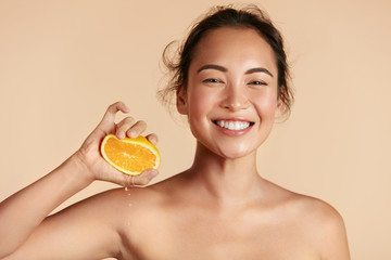 Beauty. Woman with radiant face skin squeezing orange in hand portrait. Beautiful smiling asian girl model with natural makeup, glowing facial skin and citrus fruit. Vitamin C cosmetics concept