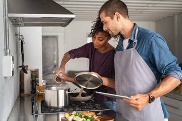 Woman adding salt in pot while cooking