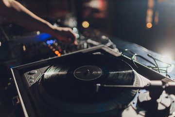 Dj hands on equipment deck and mixer with vinyl record at party.