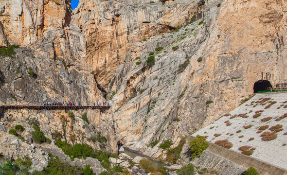 Visitors walking along the footbridge of Caminito del Rey path and train tunnel on the other side