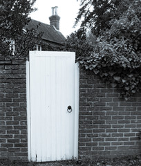 White Garden Gate Leading to an English cottage in monochrome.