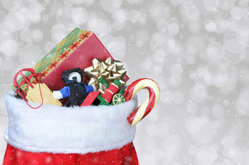 Christmas Stocking filled with toys - Bokeh Background with snow effect and copy space.