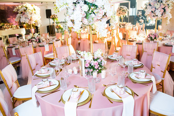 Beautiful dinner table decorated by gold accessories and flowers. Wedding. Decor