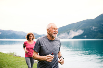 Senior pensioner couple with smartphone running by lake in nature.