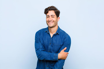 young handsome man laughing shyly and cheerfully, with a friendly and positive but insecure attitude against blue background Wall mural